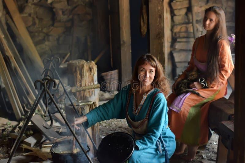 Viking kobieta przygotowywa jedzenie w garnku na ogieniu zdjęcie stock