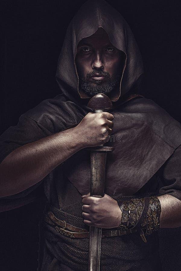 Viking-Krieger mit Klinge über dem schwarzen Hintergrund, der Klinge hält lizenzfreies stockfoto