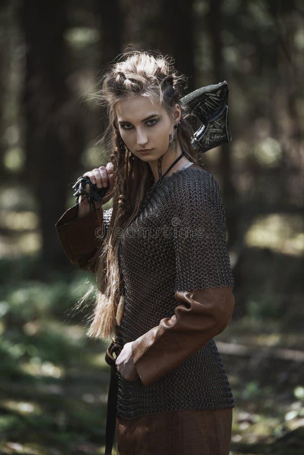 Viking kvinna med hammaren som bär traditionell krigarekläder i en djup mystisk skog arkivbilder