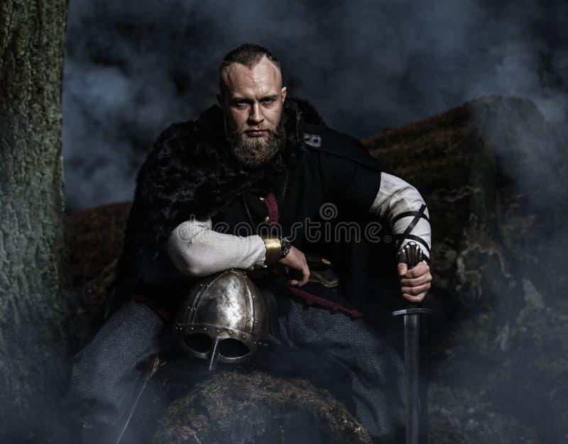 Viking met zwaard en helm op een achtergrond van rokerig bos stock afbeeldingen