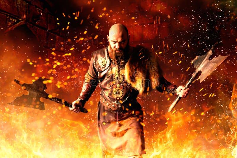 Viking mit Äxten in den Händen, die im Feuer stehen lizenzfreie stockfotografie