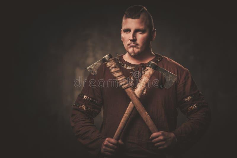 Viking sérieux avec des haches dans un guerrier traditionnel vêtx, posant sur un fond foncé images libres de droits