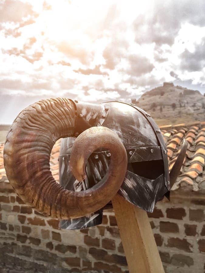 Viking-Sturzhelm mit runden großen Hörnern auf Hintergrund eines alten mit Ziegeln gedeckten Dachs stockfotos