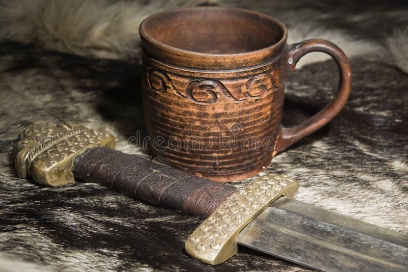 Viking svärd och ölkrus på en päls royaltyfria foton