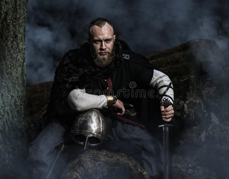 Viking with sword and helmet on a background of smoky forest stock images