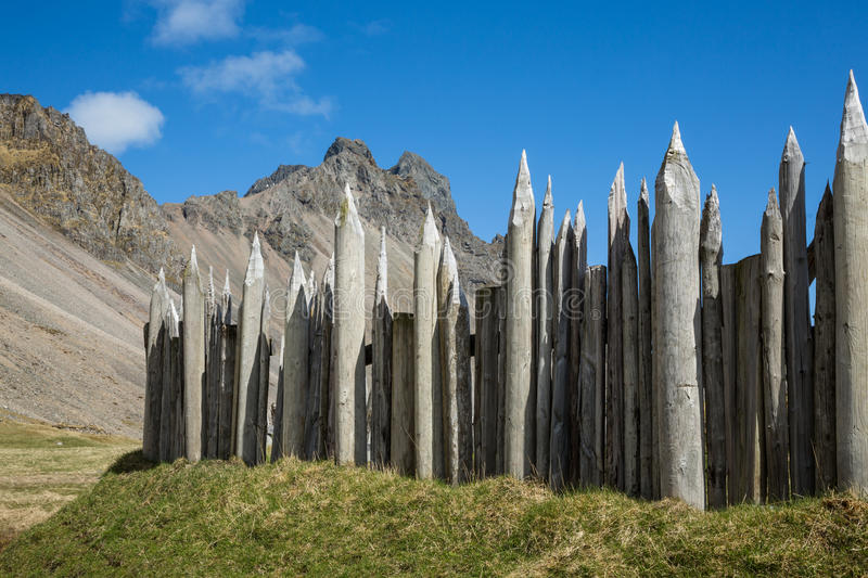 Viking village fence and rocky peaks. In a replica viking village, made for movie productions near Hofn, Iceland, this wood fence lined the outside of the royalty free stock images