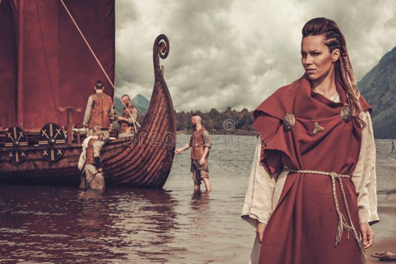 Viking-vrouw die zich dichtbij Drakkar op kust bevinden stock foto's