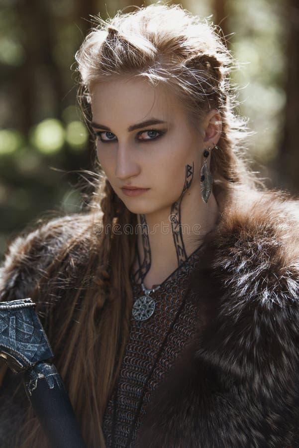 Viking-vrouw met hamer die traditionele strijderskleren in een diep geheimzinnig bos dragen royalty-vrije stock afbeelding
