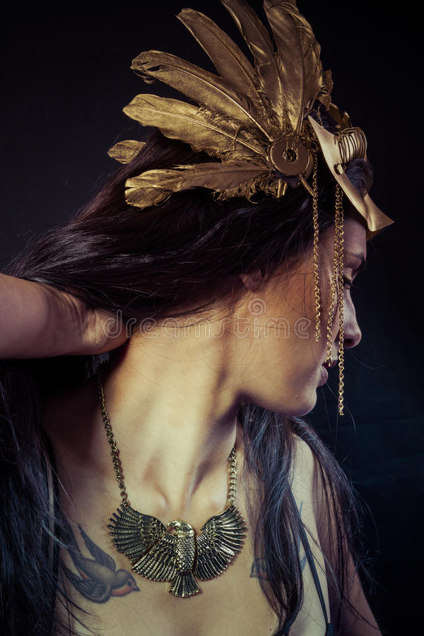 Viking, Warrior woman with gold mask, long hair brunette. Long h. Valkyrie, Golden statue concept. Arty portrait of model with golden mask and shiny lashes stock photography