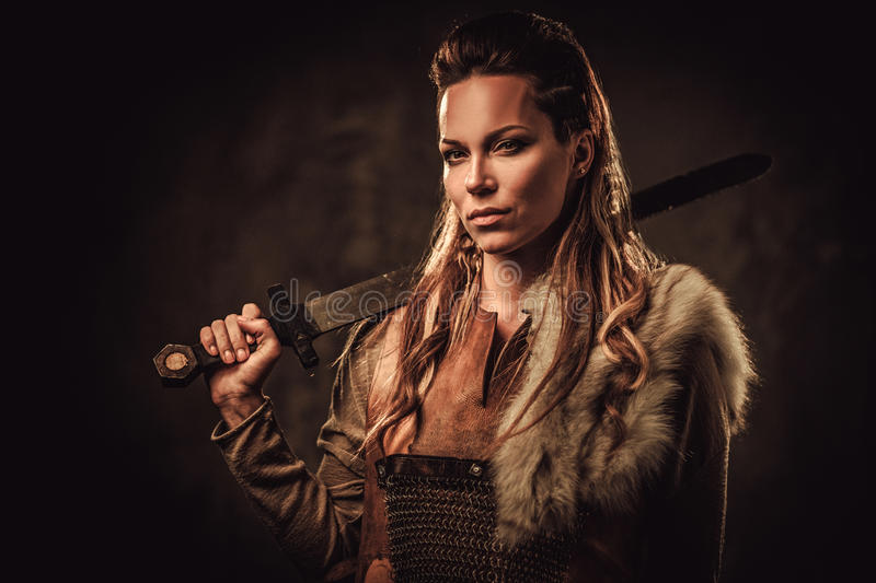 Viking woman with sword in a traditional warrior clothes, posing on a dark background. stock photo