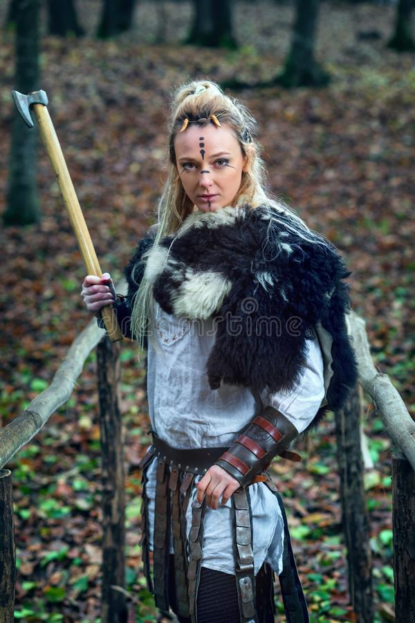 Viking woman warrior fur collar and specific makeup rising ax above head, ready to attack royalty free stock images