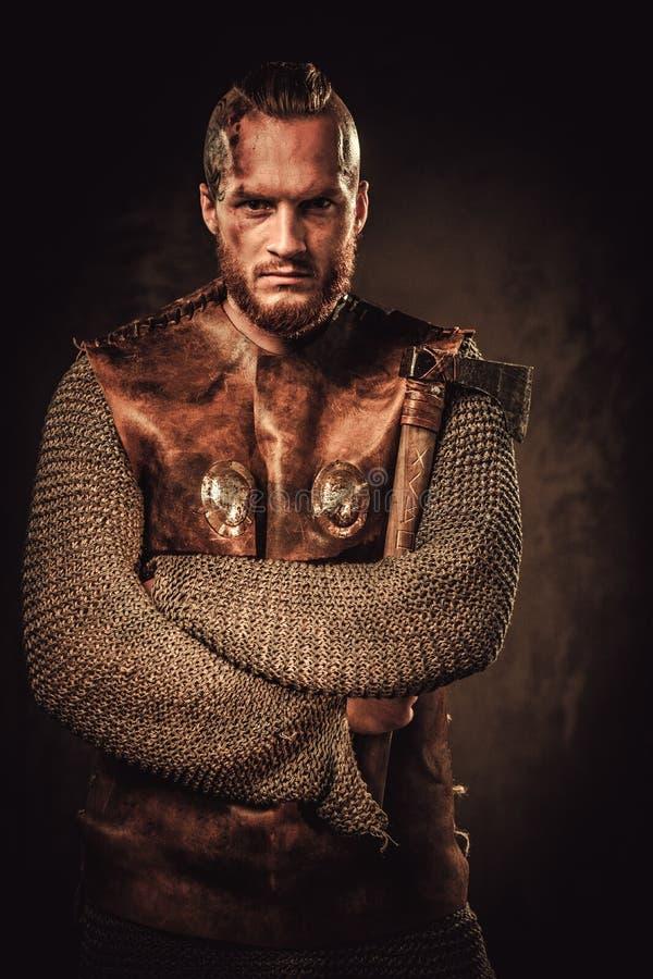 Vikingo enojado en un guerrero tradicional viste, presentando en un fondo oscuro imagen de archivo