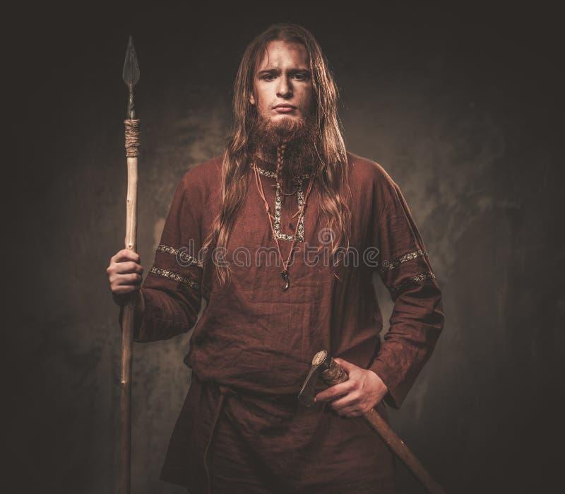 Vikingo serio con una lanza en un guerrero tradicional viste, presentando en un fondo oscuro imagen de archivo libre de regalías