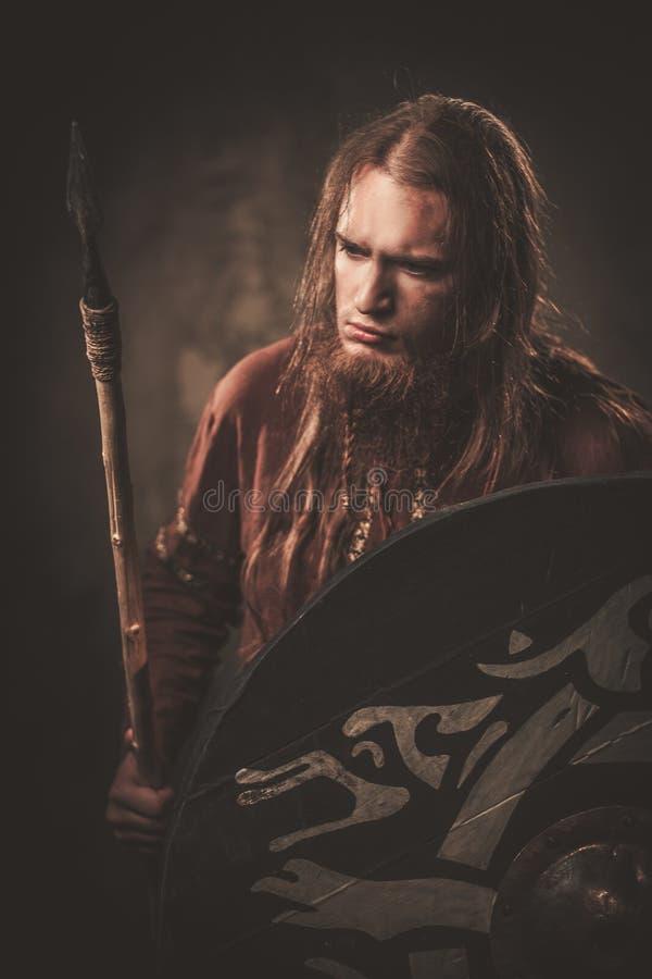Vikingo serio con una lanza en un guerrero tradicional viste, presentando en un fondo oscuro foto de archivo