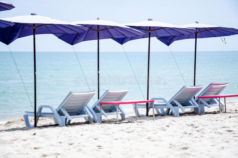 Vikningstolar med paraplyer lokaliseras på stranden för att sova och att solbada royaltyfri foto