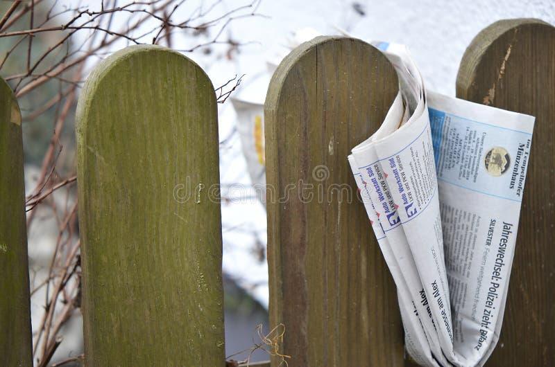 Vikt tidning som klämmas fast mellan posteringar av ett trästaket royaltyfri foto