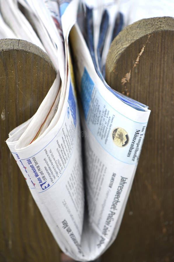 Vikt tidning som klämmas fast mellan posteringar av ett trästaket arkivbilder