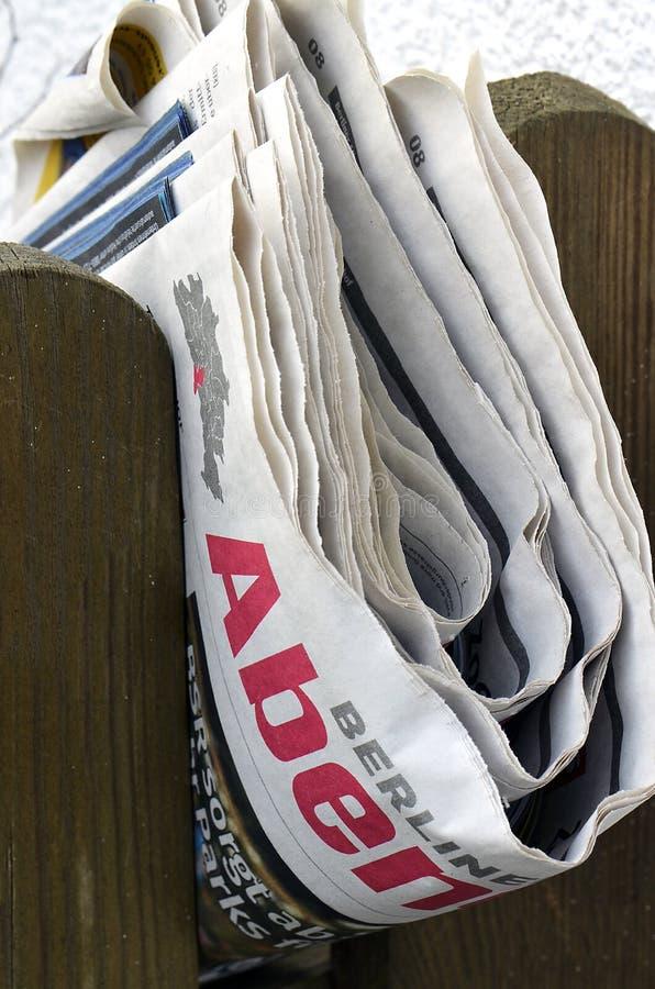 Vikt tidning som klämmas fast mellan posteringar av ett trästaket arkivbild