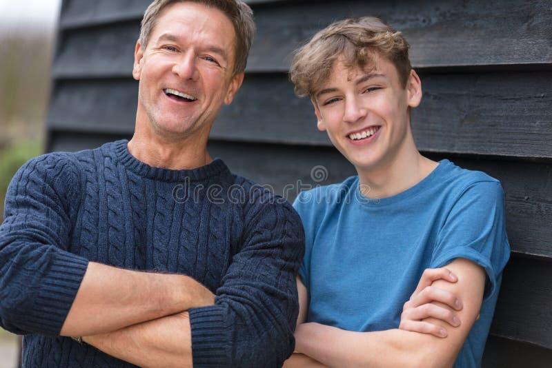 Vikta armar för lycklig mitt åldras manfader och för tonårs- son fotografering för bildbyråer