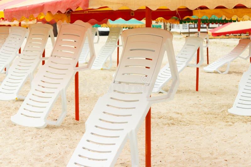 Vikta chaisevardagsrum och paraplyer på den sandiga stranden royaltyfri fotografi