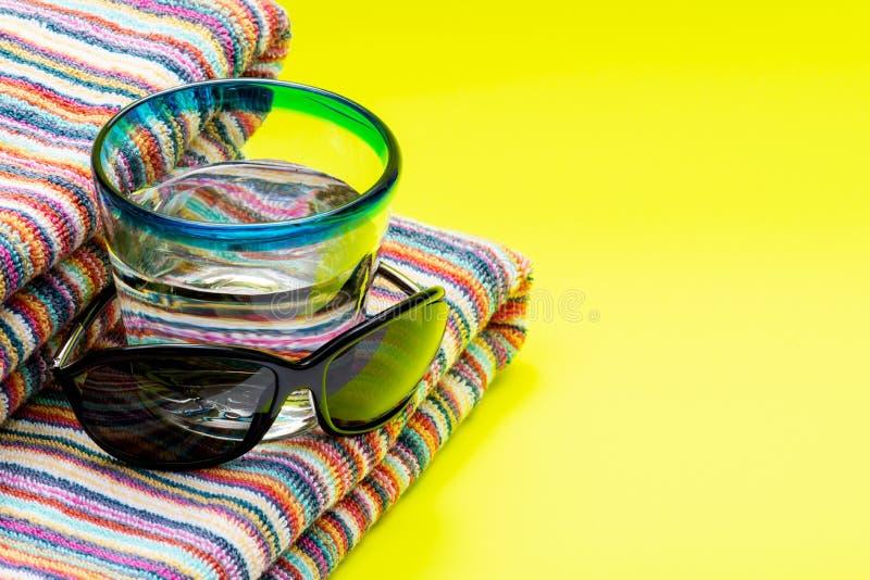 Vikta färgrika randiga organiska bomullsstrandhanddukar, blåa Rim Glass med vatten och svart solglasögon på gul bakgrund royaltyfri fotografi