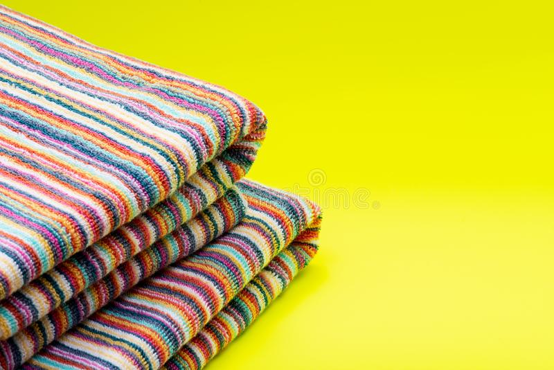 Vikta färgrika randiga organiska bomullsstrandhanddukar på ljus guling arkivbilder
