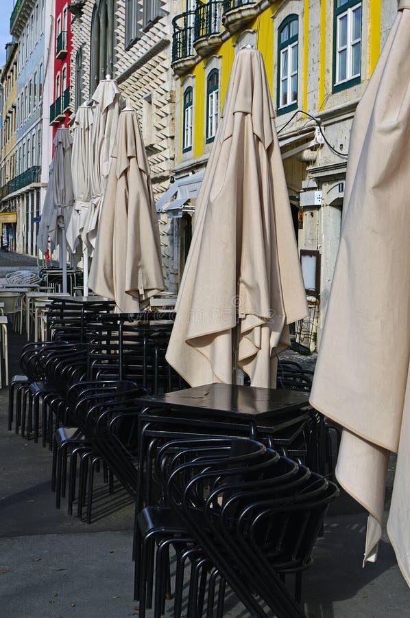 Vikta paraplyer, stolar och tabeller av restaurangen royaltyfria foton