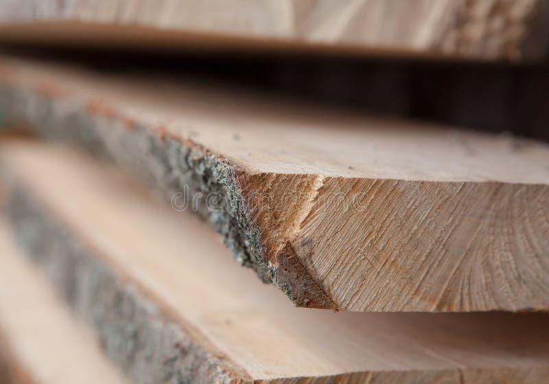 Vikta träplankor i ett sågverk Travde bräden som textur arkivbild