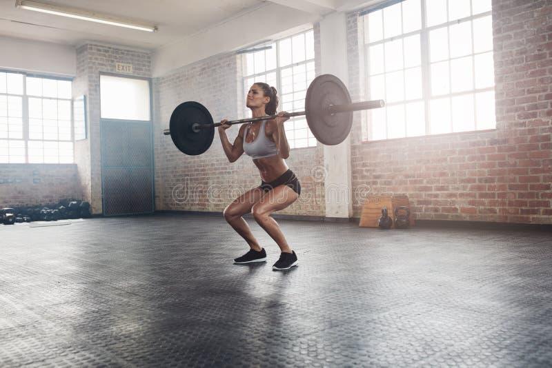 Vikter för kvinnlig idrottsman nen för kondition lyftande i idrottshall royaltyfria foton