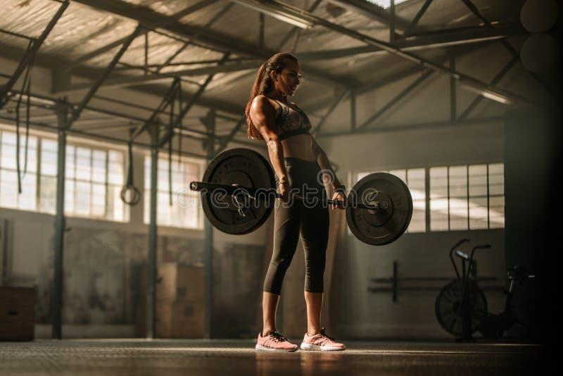 Vikter för skurkroll för arg passformkvinna lyftande i idrottshall royaltyfri fotografi