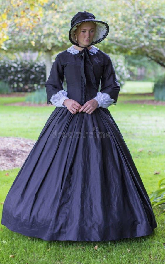 Viktorianische Frau in den schwarzen Kleiderwegen in einem Sommergarten stockbilder