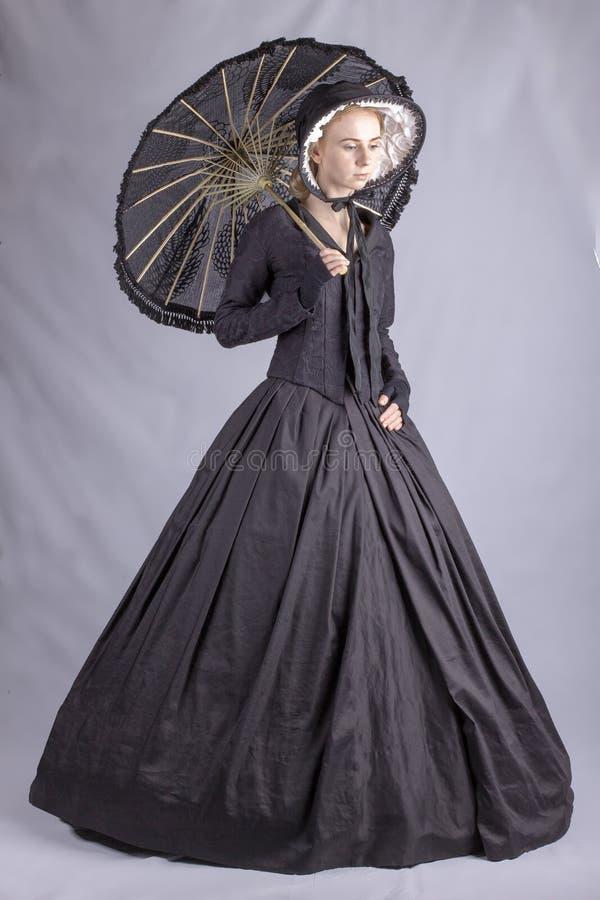 Viktorianische Frau im schwarzen Ensemble mit Sonnenschirm lizenzfreie stockfotos