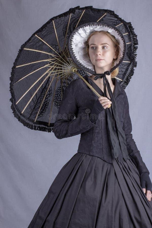 Viktorianische Frau im schwarzen Ensemble mit Sonnenschirm lizenzfreie stockfotografie