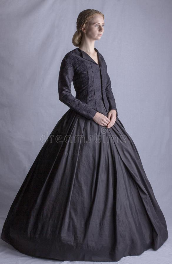 Viktorianische Frau im schwarzen Ensemble stockbild