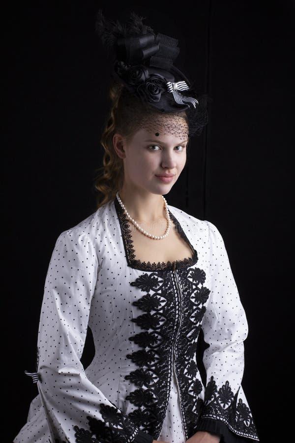 Viktorianische Frau in im Schwarzweiss-Kleid und dem Hut der hastigen Geschäftigkeit stockbild