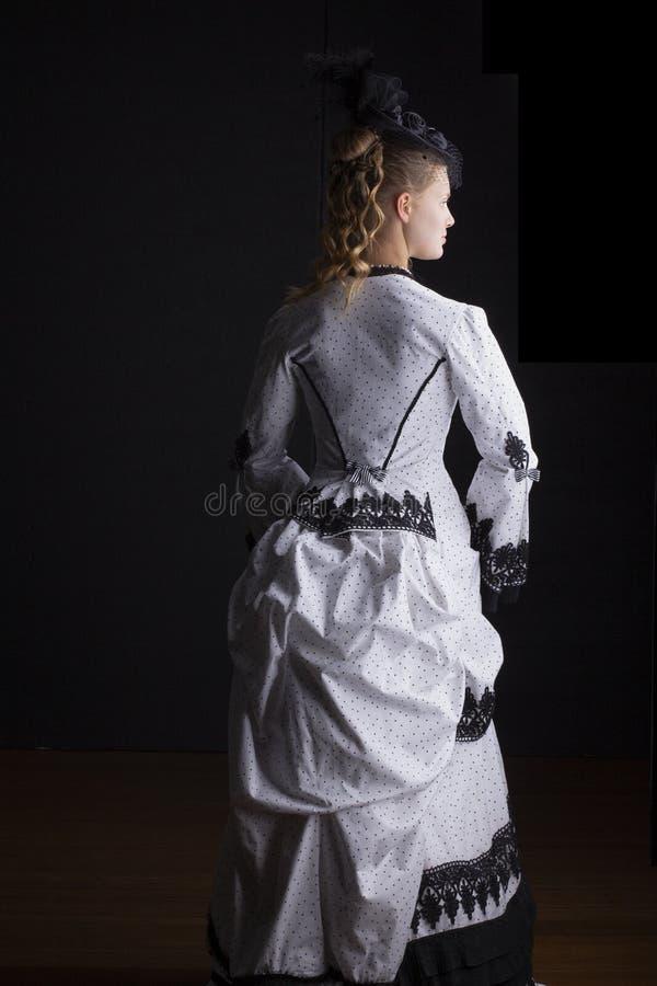 Viktorianische Frau in im Schwarzweiss-Kleid und dem Hut der hastigen Geschäftigkeit stockbilder