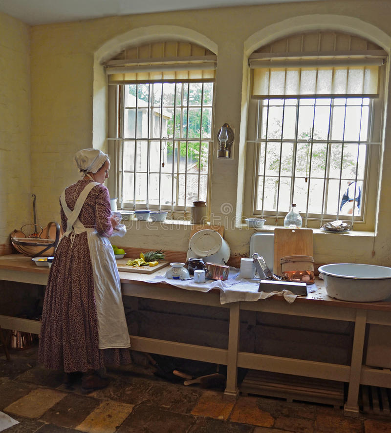 Viktorianisches Küchenmädchen, das Lebensmittel durch Fenster zubereitet stockfoto