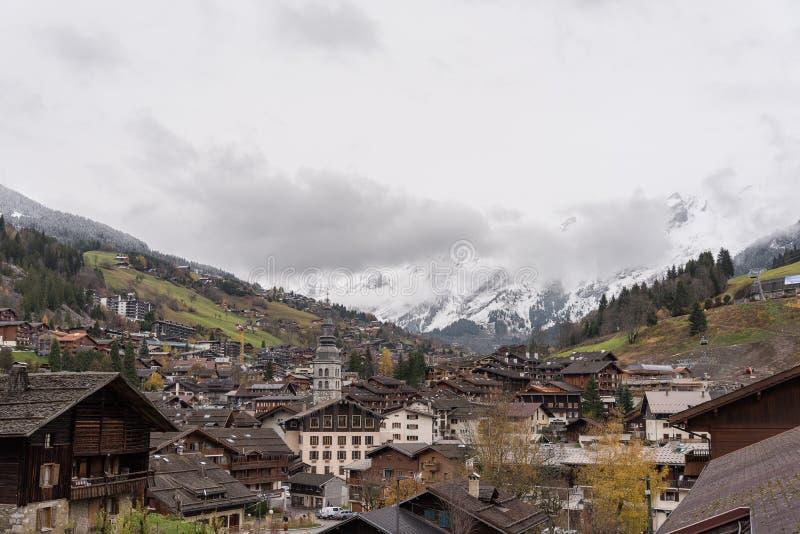 Vila alpina com a torre de sino alta no fundo dos cumes imagens de stock royalty free