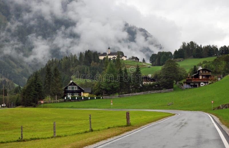 Vila com uma igreja em um monte nos cumes austríacos fotos de stock royalty free