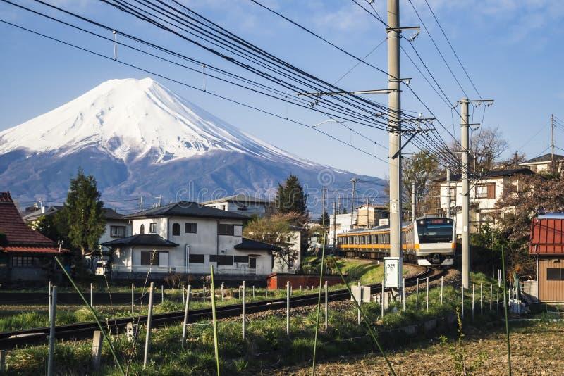 Vila da paisagem da opinião de Fuji da montanha com o trem local que passa o curso de Japão fotografia de stock