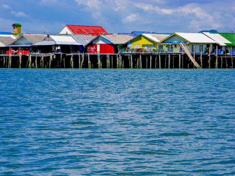 Vila de flutuação do pescador na ilha sintética com as casas coloridas do telhado e do vintage no mar azul com o céu azul claro imagens de stock royalty free