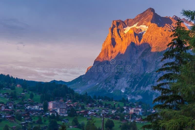 Vila de Grindelwald abaixo da cimeira de Wetterhorn durante o por do sol, Berner Oberland, cumes suíços, Suíça fotografia de stock