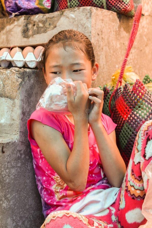 Vila de Lobesa, Punakha, Butão - 11 de setembro de 2016: Menina butanesa pequena que senta-se em escadas no bazar local, Punakha, imagens de stock royalty free