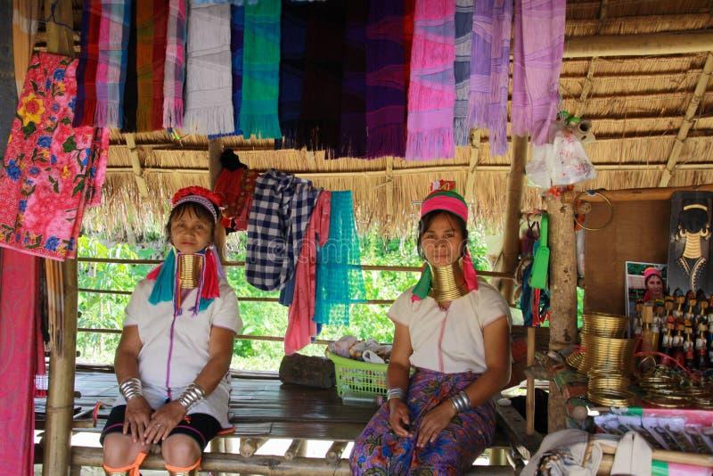 VILA DE LONGNECK KAREN, TAILÂNDIA - 17 DE DEZEMBRO 2017: Duas mulheres longas do pescoço que sentam-se na frente de uma cabana de fotos de stock