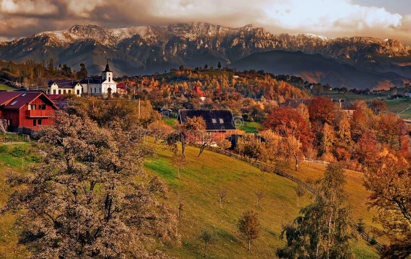 Vila de Magura na frente do maciço de Piatra Craiului, Brasov, Romênia imagens de stock