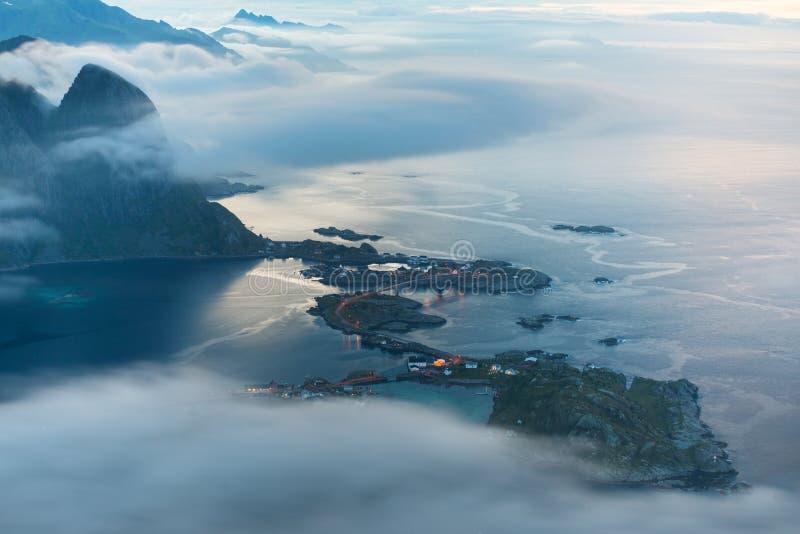 Vila de Reine nas nuvens e na névoa no amanhecer Luzes na noite, Noruega de Lofotens foto de stock royalty free