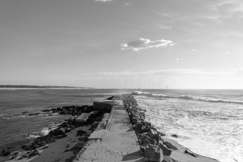 Vila do Conde shore line lighthouse. Black and white seascape scene of the bay of Vila do Conde in north Portugal royalty free stock photo