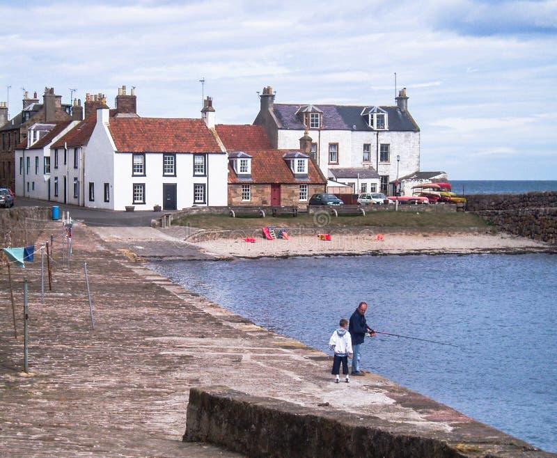 Vila escocesa, pífano, costa, Mar do Norte, entrada com homem e pesca da criança imagens de stock