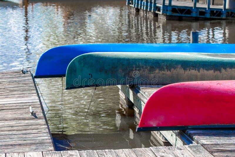 Vila f?r tre f?rgrikt kanoter som ?r uppochnerv?nt p? en skeppsdocka royaltyfria foton