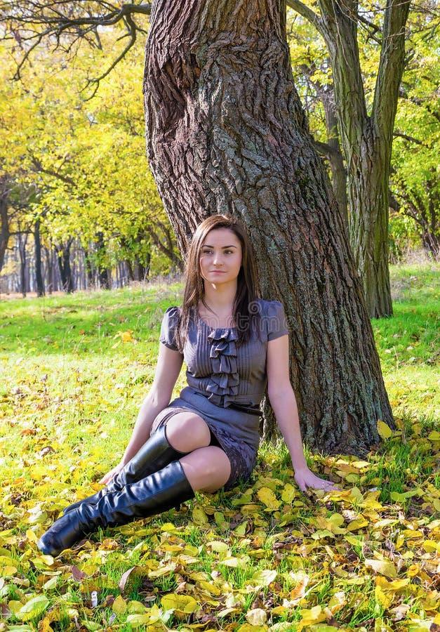 Vila kvinnasammanträde under ett träd i höstskog royaltyfri bild